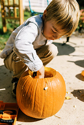 Child carving out pumpkins for halloween on their patio - p1166m2218606 by Cavan Images