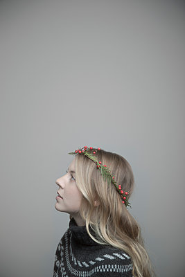 Portrait curious beautiful young blonde woman with Christmas wreath in hair - p1192m2066399 by Hero Images