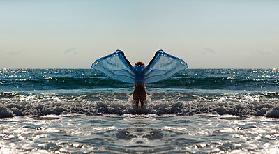 Silhouette of young woman in front of the sea holding blue cloth with outstretched arms - p300m1188584 by Andreas Jontsch