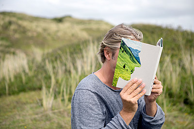 Man reading story book in the dunes, covering his face - p300m1580975 by Petra Stockhausen