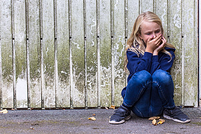Frightened girl crouching in front of wooden wall - p300m2069965 by Jana Fernow