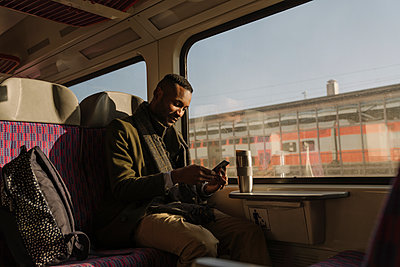 Stylish man using smartphone inside a train - p300m2155336 by Hernandez and Sorokina