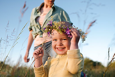 Happy boy wearing wreath while mother standing in background during sunny day - p300m2214008 by Ekaterina Yakunina