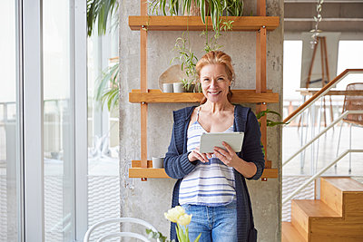 Smiling mature woman with digital tablet standing against rack at home - p300m2266096 by Jo Kirchherr
