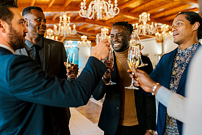 Joyful male friends talking and toasting at banquet - p300m2275015 by Ezequiel Giménez