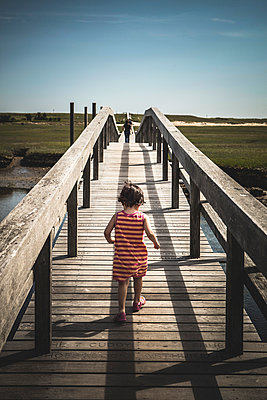 Young Girl in Striped Dress Running on Boardwalk, Rear View - p694m910932 by Roj Rodriguez photography