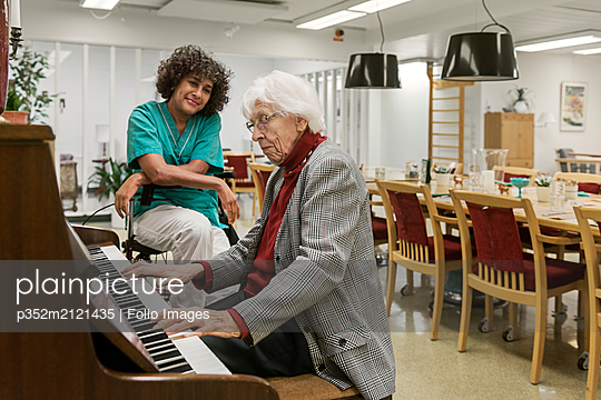 Senior woman playing piano in rest home - p352m2121435 by Folio Images