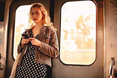 Young woman using smart phone while traveling in subway train - p1166m2153491 by Cavan Images