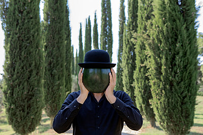 Italy, Tuscany, man surrounded by cypresses wearing a bowler hat holding a melon - p300m2104215 by Petra Stockhausen