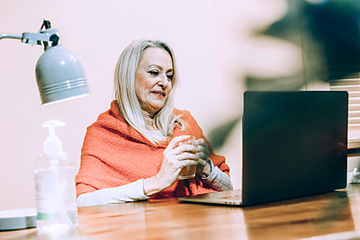 Senior woman holding drinking glass during online consultation at home - p300m2240415 by Eloisa Ramos