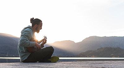 Young man singing while playing ukulele on promenade during sunny day - p300m2282051 by Josu Acosta
