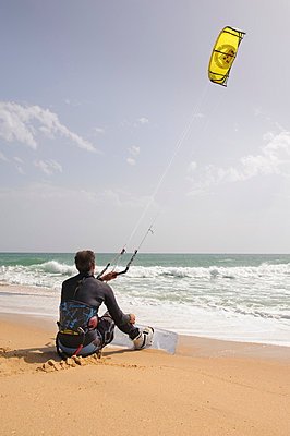 Paraglider sitting on beach waiting to take off - p312m695420 by Hans Berggren