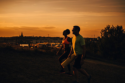 Female and male athlete walking on land during sunset - p426m2270764 by Maskot