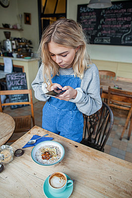 Young woman in cafe, using smartphone - p429m1206958 by Janeycakes Photos