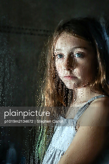 Portrait of a girl behind pane  - p1019m2134672 by Stephen Carroll