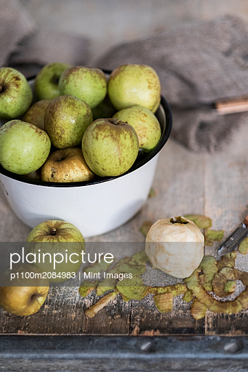 High angle close up of white bowl with green apples. - p1100m2084983 by Mint Images