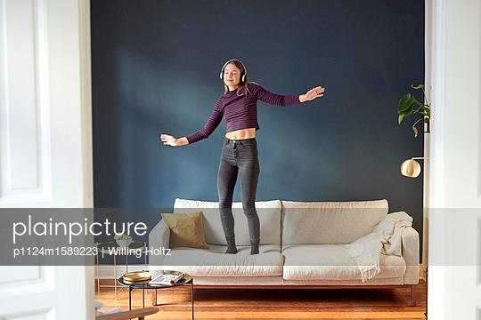 Junge Frau mit Kopfhörern tanzt auf dem Sofa - p1124m1589223 von Willing-Holtz