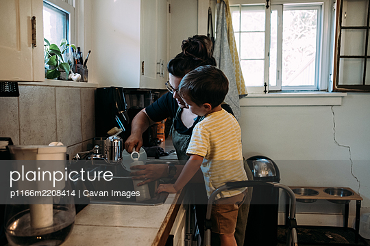 Mother and Child working together at kitchen sink - p1166m2208414 by Cavan Images