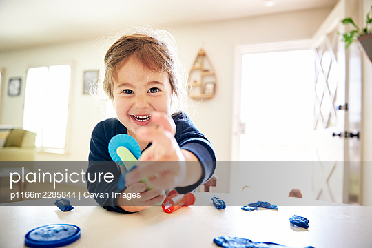 Portrait of cheerful girl playing with toys on table at home - p1166m2285844 by Cavan Images