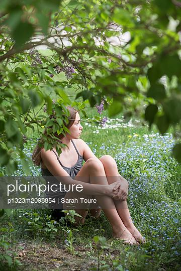 portrait of a teenage girl sitting in grass - p1323m2098854 von Sarah Toure