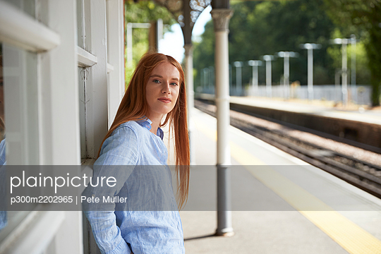 Beautiful woman standing at railroad station platform - p300m2202965 by Pete Muller