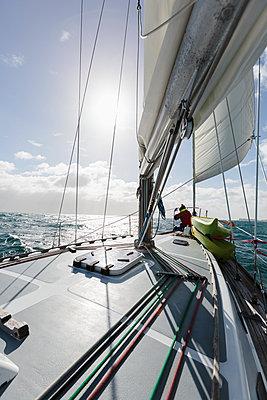 Woman at bow of sailboat on sunny ocean, Vava'u, Tonga, Pacific Ocean,  - p1023m2024437 by Martin Barraud