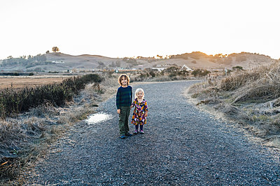 Portrait of posed sibllings holding hands at natural park - p1166m2095095 by Cavan Images