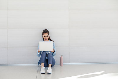 Woman sitting on floor with laptop by white wall - p1166m2095884 by Cavan Images