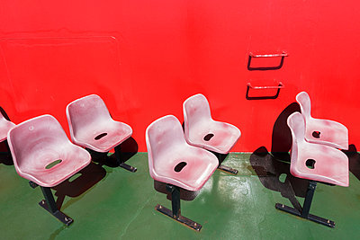 Faded red plastic seats on the deck of a ferry - p1302m1148525 by Richard Nixon
