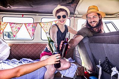 Happy friends inside van clinking bottles - p300m2041829 by Jo Kirchherr