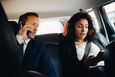 Businessman talking on mobile phone while sitting by female colleague in taxi - p426m1517945 by Maskot