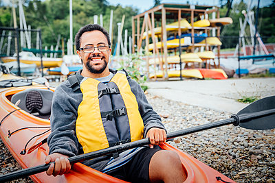 Mixed Rave man sitting in kayak holding paddle - p555m1303913 by Inti St Clair photography