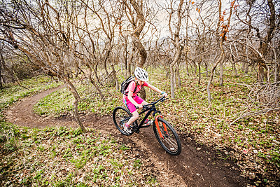 Caucasian girl riding bicycle on forest path - p555m1490971 by Mike Kemp