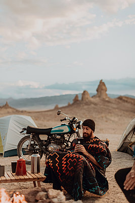 Motorcyclist road trippers around camp fire, Trona Pinnacles, California, US - p924m2068170 by Peter Amend
