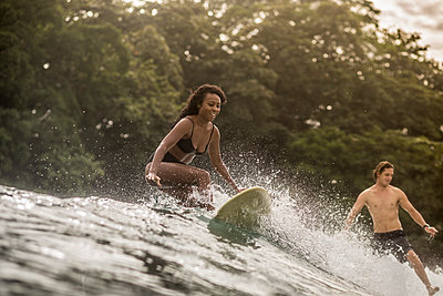 Indonesia, Java, happy woman and man surfing - p300m1356319 by Konstantin Trubavin