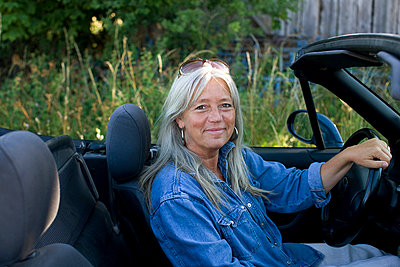 Mature woman sitting inside convertible car - p31226728f by Bjurling, Hans