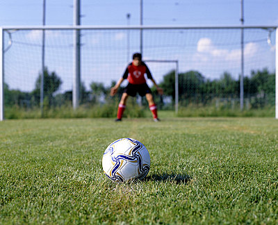 football lying on penalty spot with goalkeeper in background  - p3161394f by Bernd Eberle