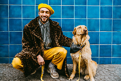 Full length of smiling man crouching by dog against blue tiled wall - p426m2279788 by Maskot
