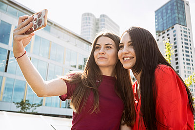 Two women standing in a city taking a selfie of themselves with a mobile phone - p429m2182651 by Tamboly