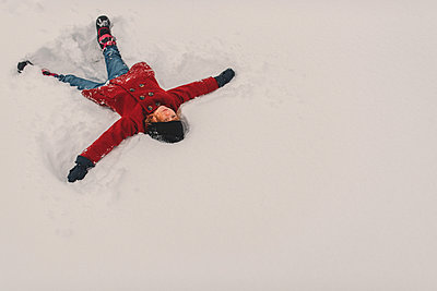 Girl lying on snow - p924m1230219 by Kymberlie Dozois Photography
