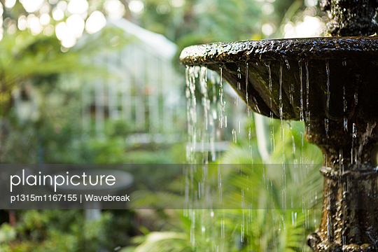 Close-up of flowing fountain in community garden - p1315m1167155 by Wavebreak