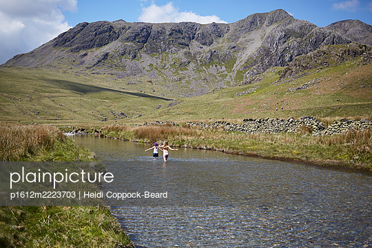 Zwei Mädchen spielen in einem Fluss - p1612m2223703 von Heidi Coppock-Beard