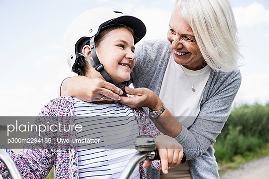 Smiling woman putting cycling helmet to girl while standing by bicycle - p300m2294185 by Uwe Umstätter