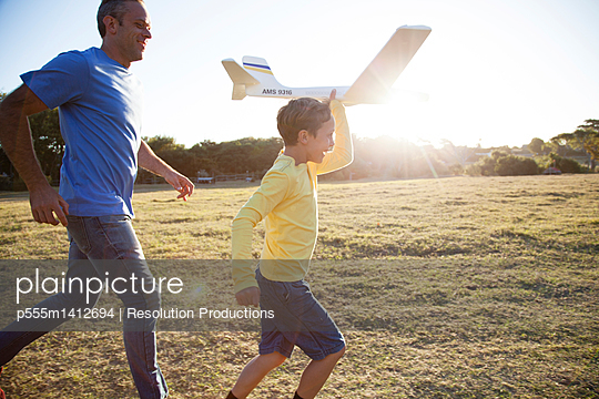 Caucasian father and son flying model airplane in field - p555m1412694 by Resolution Productions