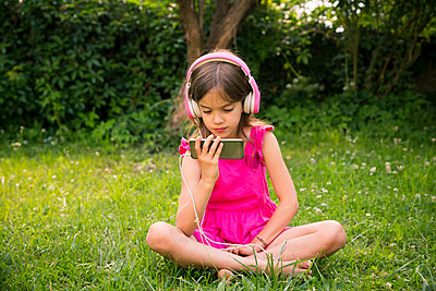 Portrait of girl sitting on a meadow using smartphone and pink headphones - p300m2070287 by Larissa Veronesi