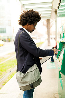 Spain, Barcelona, businessman using ticket machine at tram stop in the city - p300m2104480 by Valentina Barreto