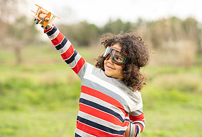 Cute boy wearing aviator glasses playing with wooden toy airplane - p300m2266363 by Jose Carlos Ichiro