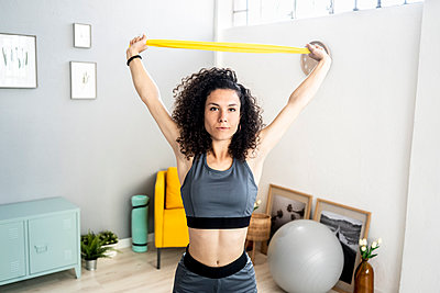 Woman exercising with resistance band at home - p300m2275439 by Giorgio Fochesato