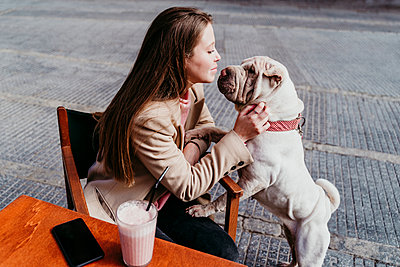 Woman looking at pet while sitting at sidewalk cafe - p300m2281639 by Eva Blanco