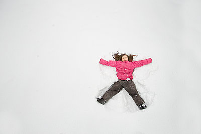 Caucasian girl making snow angel - p555m1409055 by Shestock